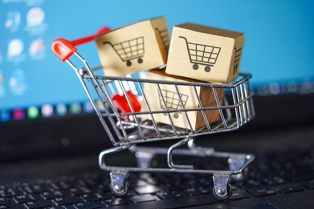 Shopping cart on notebook keyboard, online business import export concept.