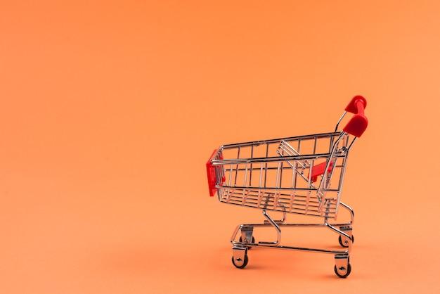 オレンジ色の背景のショッピングカート。