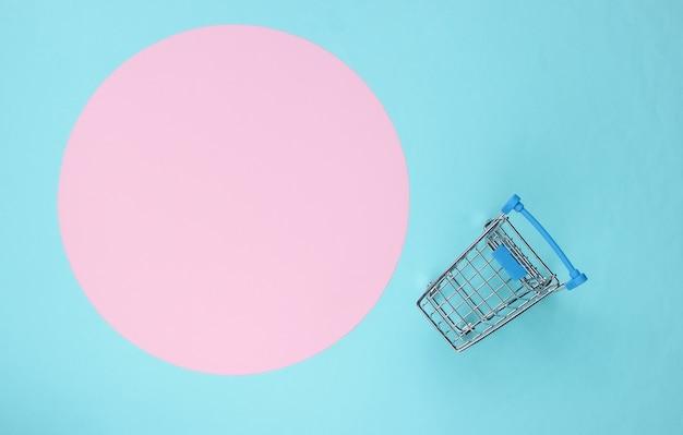 コピースペースのためのピンクのパステルサークルと青い背景のショッピングカート。ミニマルなショッピングコンセプト、買い物中毒。上面図