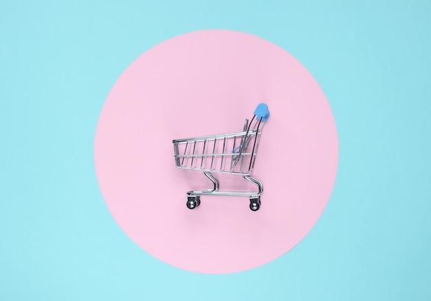 ピンクのパステルサークルと青い背景のショッピングカート。ミニマルなショッピングコンセプト、買い物中毒。上面図