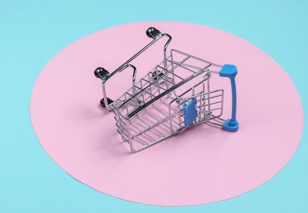ピンクのパステルサークルと青い背景のショッピングカート。ミニマルなショッピングコンセプト、買い物中毒。