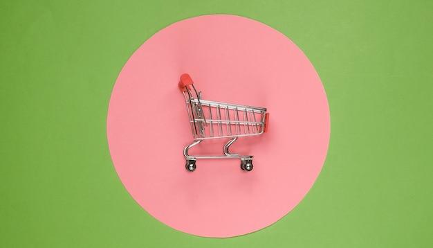분홍색 파스텔 원이 있는 녹색 배경의 쇼핑 카트. 최소한의 쇼핑 개념, 쇼핑 중독.