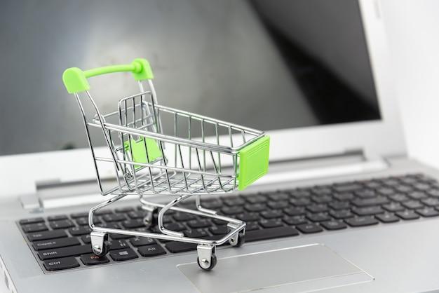 노트북 배경에 쇼핑 카트입니다. 쇼핑, 투자, 구매 개념.
