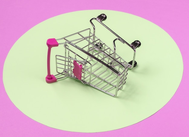 노란색 파스텔 원이 있는 분홍색 배경의 쇼핑 카트. 최소한의 쇼핑 개념, 쇼핑 중독.