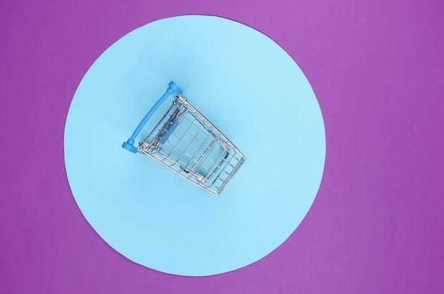 青いパステルサークルと紫色の背景のショッピングカート。ミニマルなショッピングコンセプト、買い物中毒。
