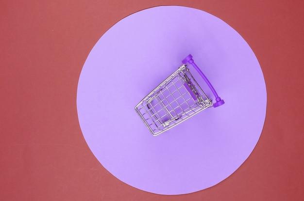 보라색 파스텔 원이 있는 빨간색 배경의 쇼핑 카트. 최소한의 쇼핑 개념, 쇼핑 중독.