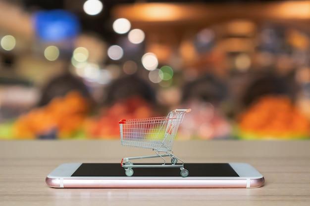 Корзина на смартфоне на деревянном столе с супермаркетом