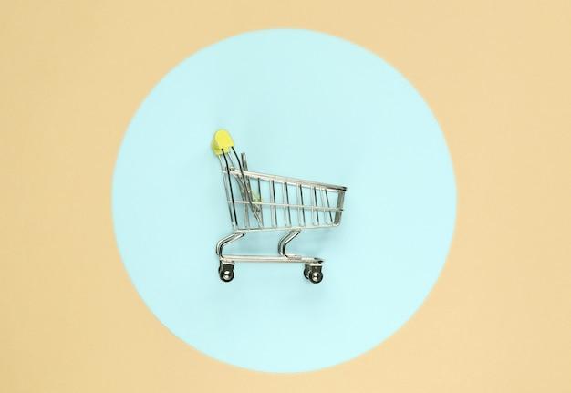 파란색 파스텔 원이 있는 노란색 배경의 쇼핑 카트. 최소한의 쇼핑 개념, 쇼핑 중독. 평면도
