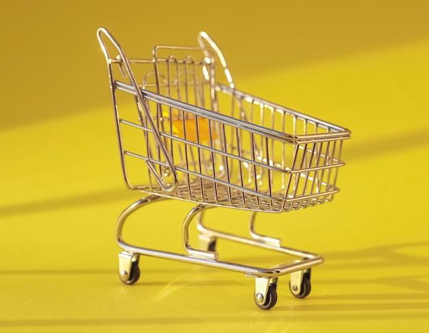 Корзина на желтом фоне с тележкой супермаркета дневного света
