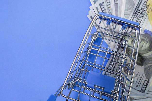 Shopping cart on one hundred dollar bills.