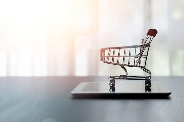 日光とタブレットのショッピングカートまたはトロリー。オンラインショッピングの概念。
