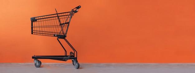 Shopping cart on an orange background Premium Photo