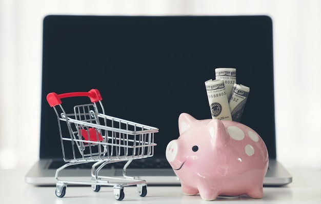 Shopping cart and piggy bank with laptop on the desk