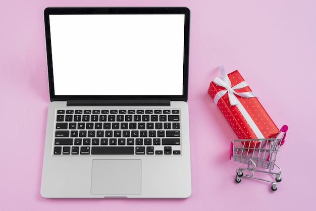 Shopping cart and small present near laptop