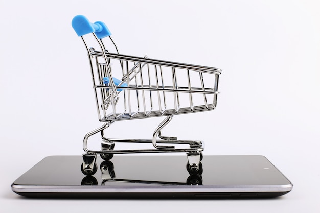 Shopping cart stands on the smartphone. online sales concept.
