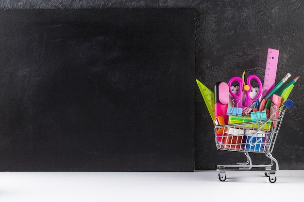 Shopping cart stocked with school supplies and a blackboard background