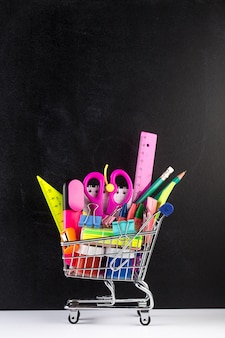 Shopping cart stocked with school supplies and a blackboard