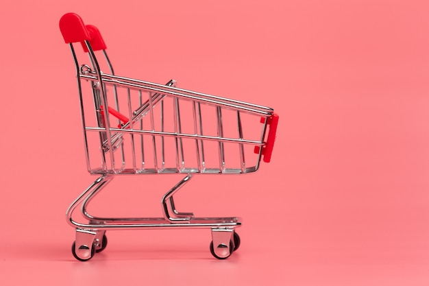Shopping cart or supermarket trolley on pink background