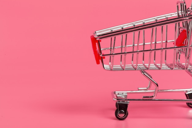 Shopping cart or supermarket trolley on pink