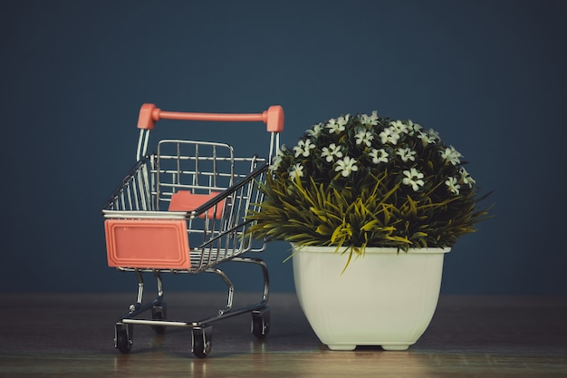 Shopping cart or supermarket trolley with little tree on table