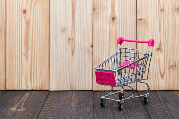 Shopping cart or supermarket trolley on wood