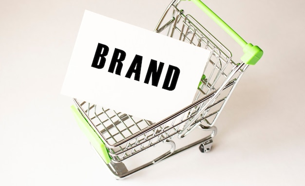 Shopping cart and text brand on white paper. shopping list concept on light surface