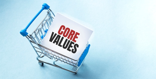 Shopping cart and text core values on white paper note list.