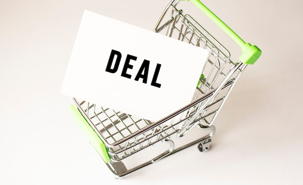 Shopping cart and text deal on white paper. shopping list concept on light.