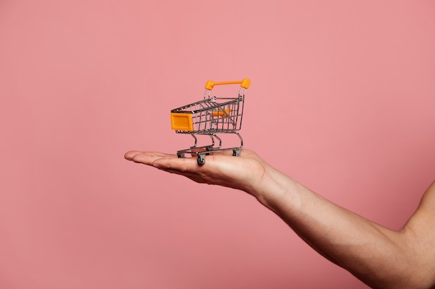 A shopping cart. toy shopping cart, which is standing on a man's hand.
