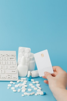 Игрушечная тележка с лекарствами и клавиатурой. таблетки, блистерные упаковки, медицинские флаконы, термометр, защитная маска на синем фоне.