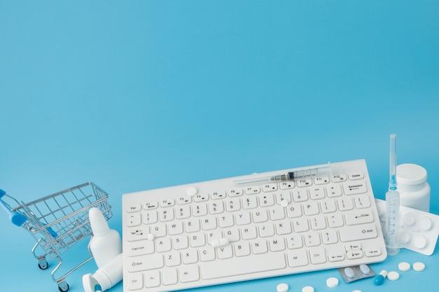 医薬品とキーボードを備えたショッピングカートのおもちゃ。丸薬、ブリスターパック、医療用ボトル、温度計