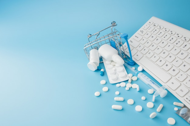 Shopping cart toy with medicaments and keyboard. pills, blister packs, medical bottles, thermometer, protective mask on a blue background. top view with place for your text