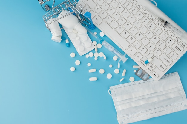 Shopping cart toy with medicaments and keyboard. pills, blister packs, medical bottles, thermometer, protective mask on a blue background.. top view with place for your text