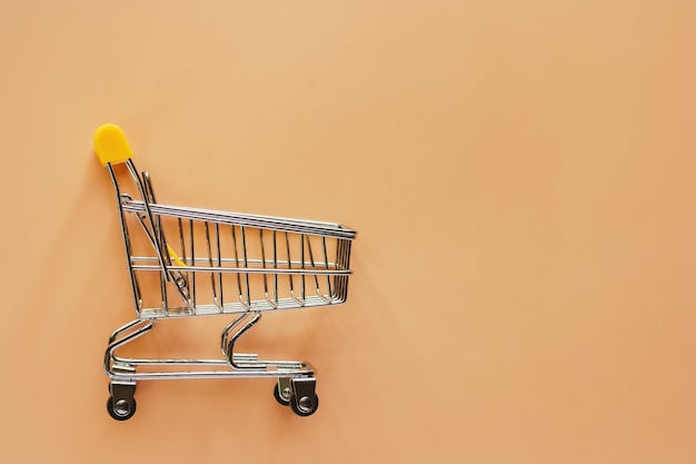 Shopping cart or trolley on beige color background for carrying loads