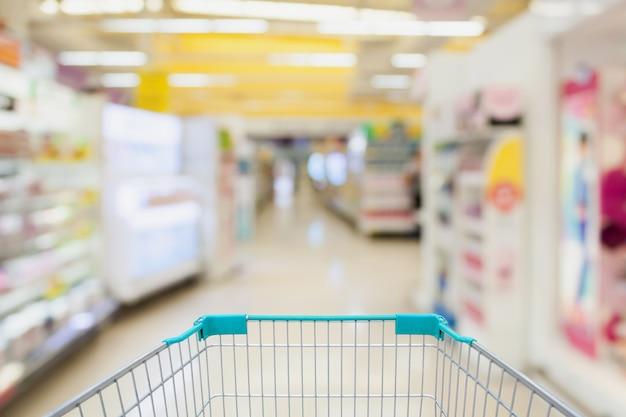 슈퍼마켓 통로 우유 요구르트 냉동 식품 냉동고 및 선반에서 쇼핑 카트보기 및 고객 defocus 배경