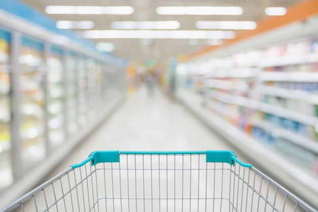Shopping cart view with supermarket aisle abstract blur frozen and dairy products in refrigerator shelves background