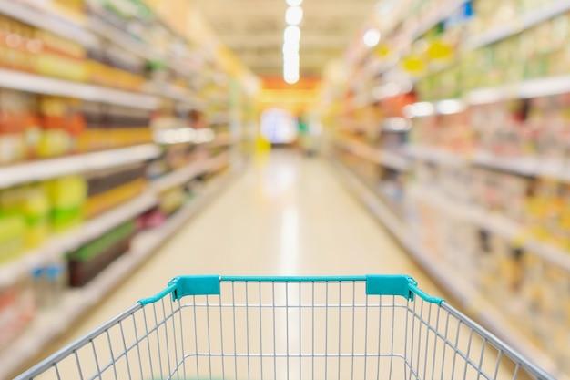 スーパーマーケットの通路の棚の内部の抽象的なぼかしの焦点がぼけた背景のあるショッピングカートビュー