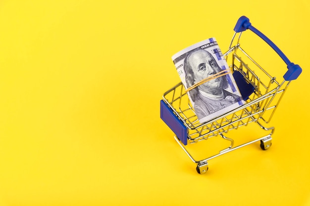Корзина с рулоном стодолларовых купюр на желтом фоне