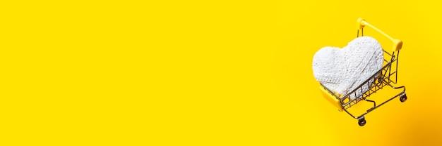 흰색 손수 마음으로 쇼핑 카트 밝은 노란색 배경에 날아간 다. 배너.