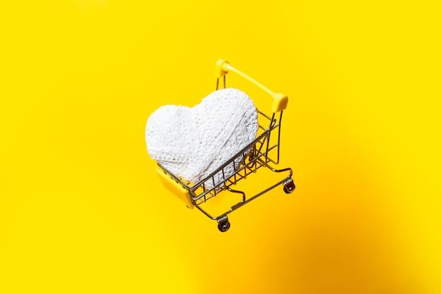 흰색 손수 마음으로 쇼핑 카트 밝은 노란색 배경에 날아간 다.