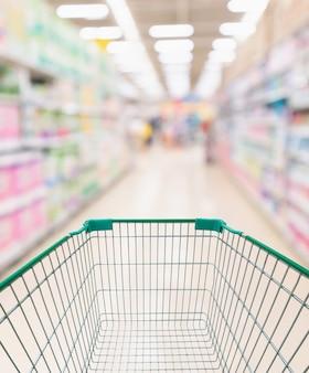 추상 흐리게 슈퍼마켓 통로가있는 쇼핑 카트 및 다양한 화장지 디스플레이가있는 선반