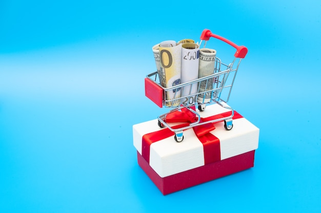 Shopping cart with american and european banknotes inside stand on gift box decorated with ribbon and bow