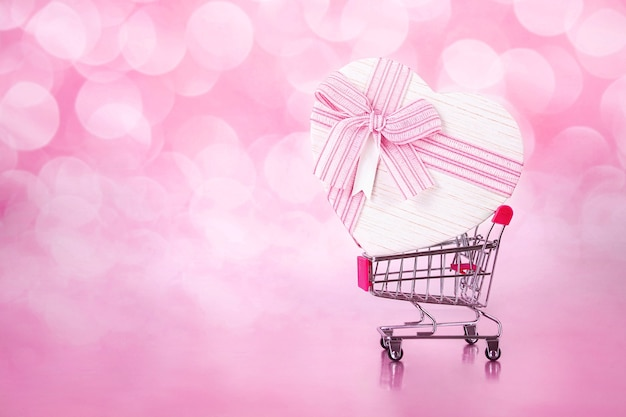 Shopping cart with big gift with form of heart on pink with bokeh backgrounds.love shopping