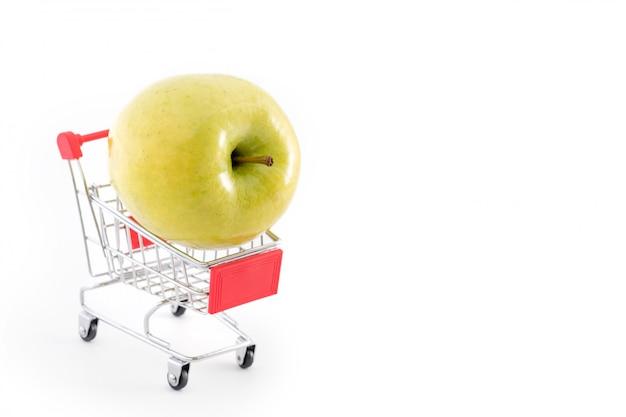 白の大きな青リンゴとショッピングカート。スーパーから果物を買う。セルフサービスのスーパーマーケットのフルショッピングトロリーカート。販売、豊富、収穫のテーマ。テキストのcopyspace。