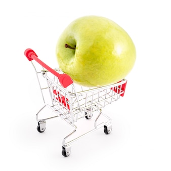Shopping cart with big green apple on white. buying fruits from supermarket. self-service supermarket full shopping trolley cart. sale, abundance, harvest theme
