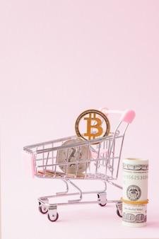 복사 공간 분홍색 배경에 bitcoin 동전과 달러 쇼핑 카트