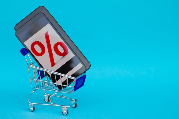 Shopping cart with black mobile phone with red discount percent sign on blue background. copy space