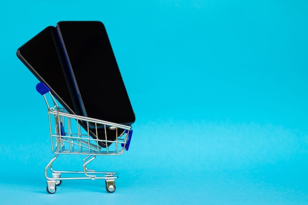 Shopping cart with black mobile phones on blue background. copy space