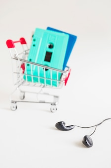 Shopping cart with cassette tapes and black earphone over white background