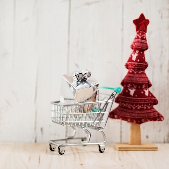 Shopping cart with christmas gift and tree